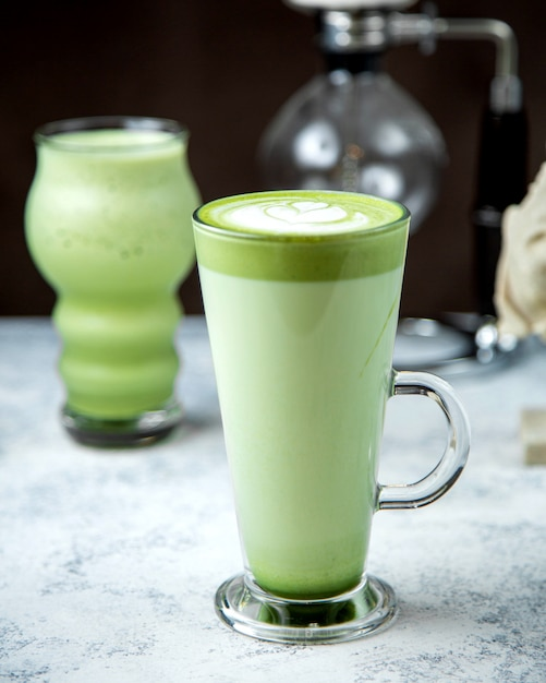 A glass of matcha green tea with latte art on top Free Photo