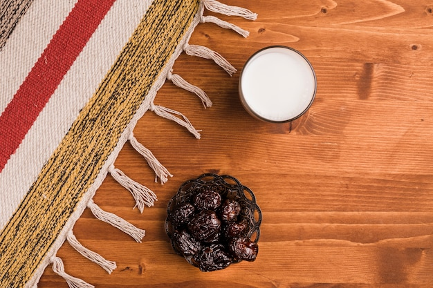 Glass of milk near saucer with sweet prunes and mat Free Photo
