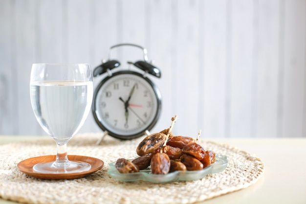 Glass of mineral water and dates with alarm clock showing 6 oclock