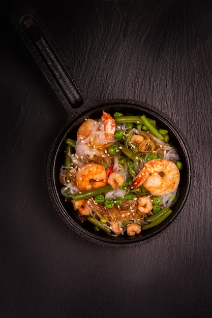 Glass noodle with shrimps and green vegetables in cast-iron pan. healthy food concept. Premium Photo