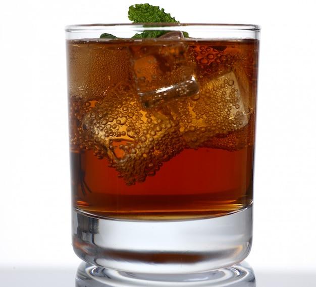 Стакан алкогольного напитка со льдом в студии Premium Фотографии