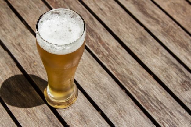 晴れた日に木の表面に冷たいビールのグラス 無料写真