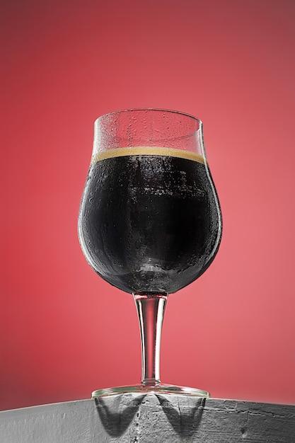 Стакан холодного пенистого темного пива на старый деревянный стол Бесплатные Фотографии