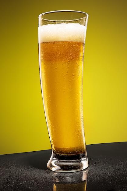 Стакан холодного пенистого светлого пива на старый деревянный стол Бесплатные Фотографии