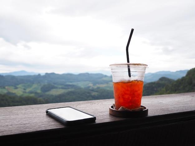 雨空を背景に山の緑の森の上のヴィンテージの木製テーブルにアイスティーとスマートフォンのガラス。 Premium写真