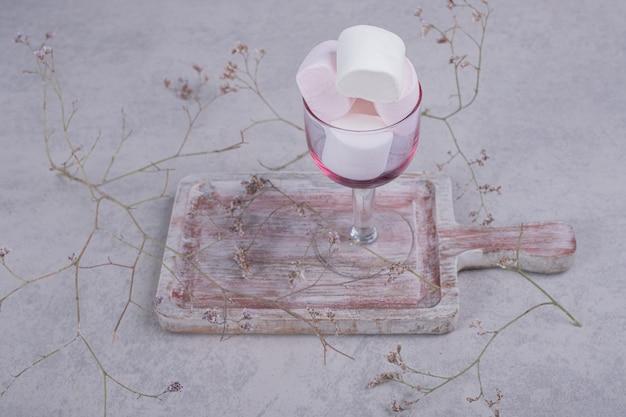 植物と木の板にマシュマロのガラス。高品質の写真 無料写真