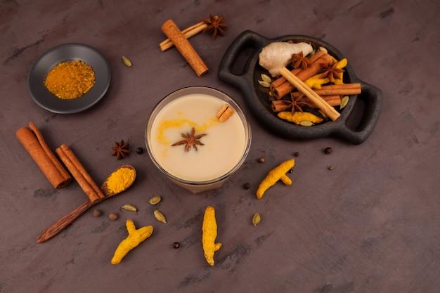 Стакан чая масала или карак-чай. набор ингредиентов для популярных индийских напитков. Premium Фотографии