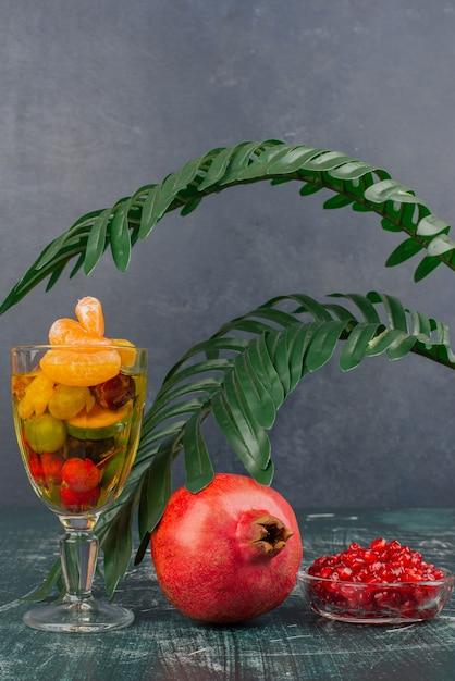 Стакан смешанных фруктов и граната с семенами на мраморном столе Бесплатные Фотографии