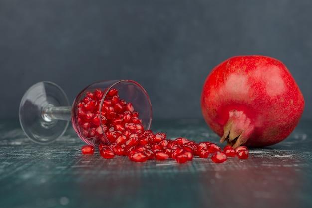 Стакан семян граната и граната на мраморной поверхности Бесплатные Фотографии