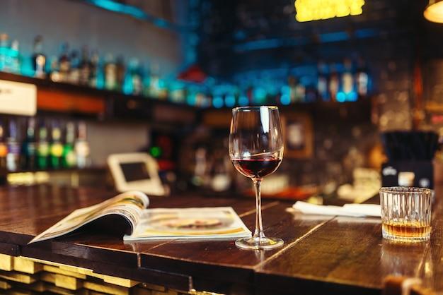 Бокал красного вина и открытое меню на деревянной барной стойке. концепция ночного образа жизни Premium Фотографии