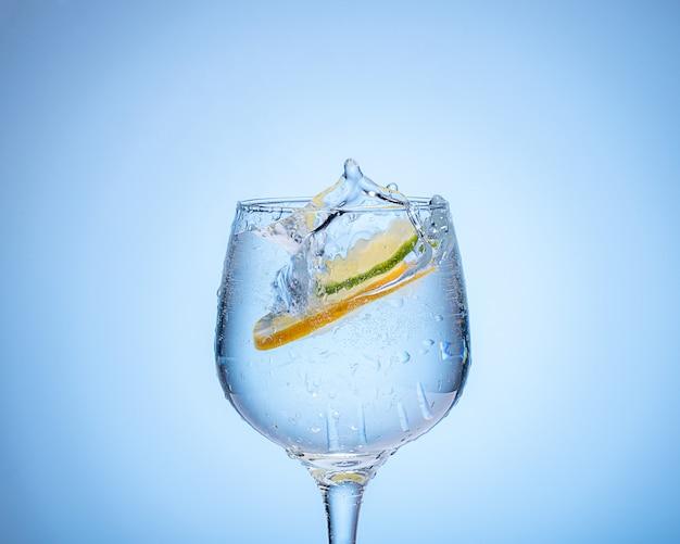 Стакан воды с лимоном и цветными ледяными шариками на голубом фоне градиента. Premium Фотографии