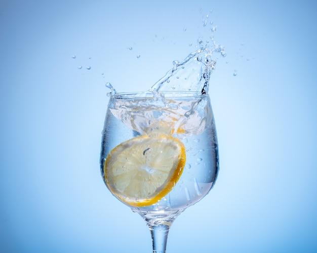 Стакан воды с лимоном упал и всплеск на голубом фоне градиента. Premium Фотографии