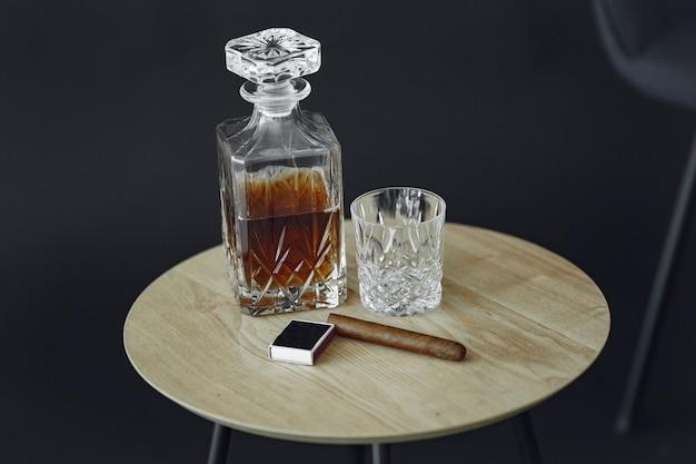 テーブルの上の葉巻とウイスキーのガラス。アルコールと葉巻の写真をクローズアップ。 無料写真