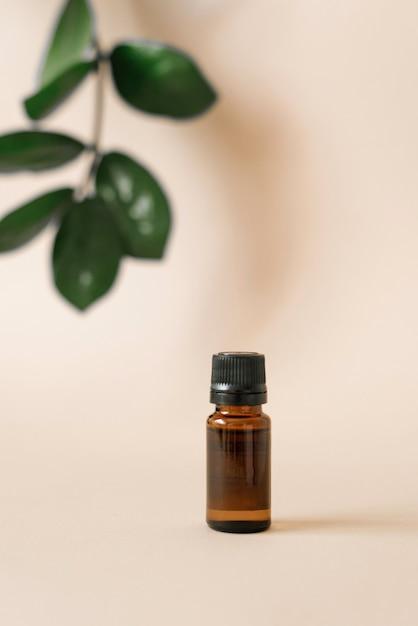 Стеклянная бутылка масла и листья тропических растений Premium Фотографии