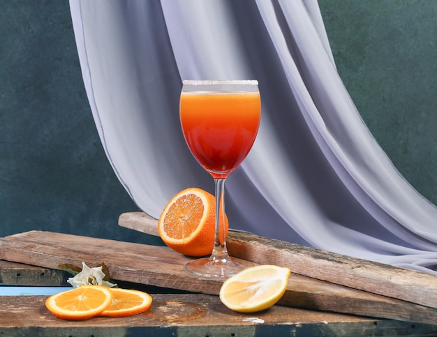 A glass of orange cocktail on a piece of wood. Free Photo