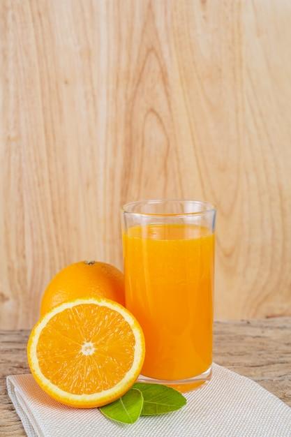 Glass of orange juice placed on wood. Free Photo