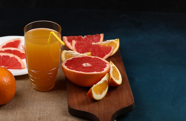 A glass of orange juice with sliced fruits. Free Photo