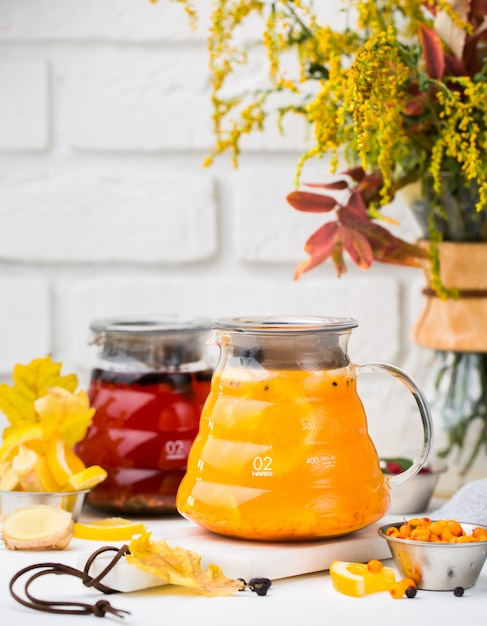 Glass pitchers with red tea and cape gooseberry tea Free Photo