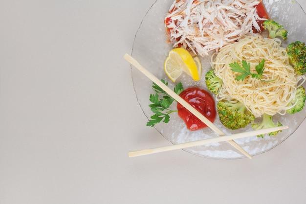 Стеклянная тарелка спагетти, курицы и овощей на белой поверхности Бесплатные Фотографии