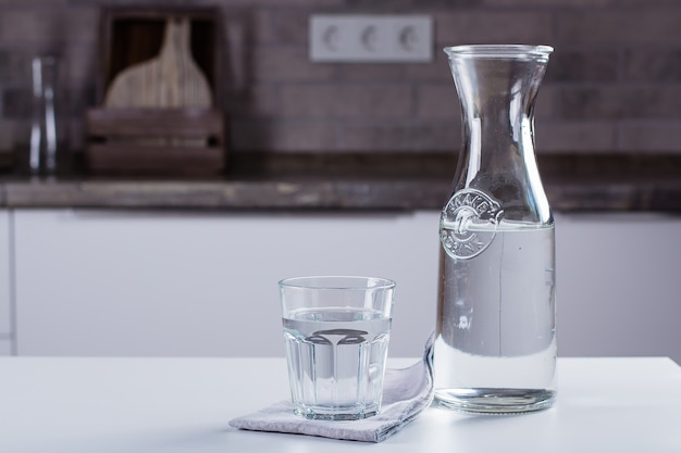 Glass of pure water and bottle on kitchen table. clean concept Premium Photo