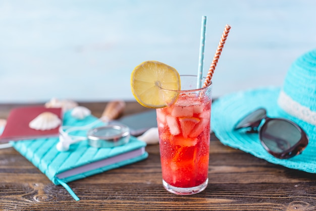 Glass of red lemonade drink with lemon and fruit and straw on the table Premium Photo