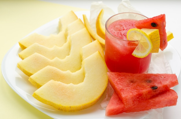Glass of red watermelon smoothie and slices of melon and watermelon Premium Photo