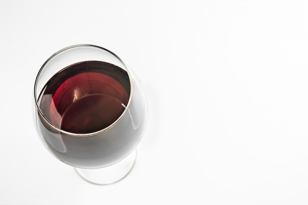 Glass of red wine, copy space, isolated. spanish emerald wine in a glass with a high stem. Premium Photo