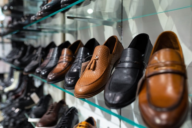 Glass shelves with man's shoes in a shop, focus on shoes Premium Photo