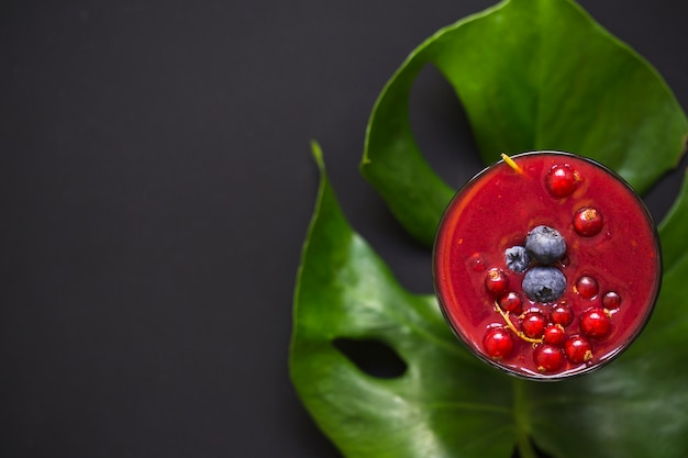 Glass of smoothie with berries on monstera leaf over the black background Free Photo