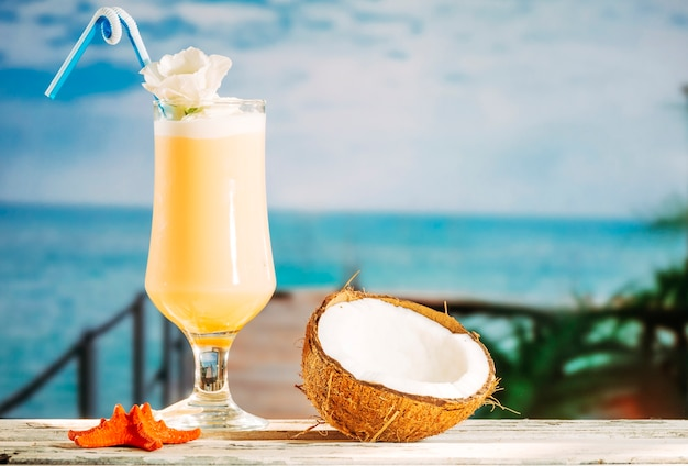 Glass of soft yellow drink orange starfish and cracked coconut Free Photo