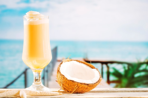 Glass of soft yellow drink starfish and cracked coconut Free Photo