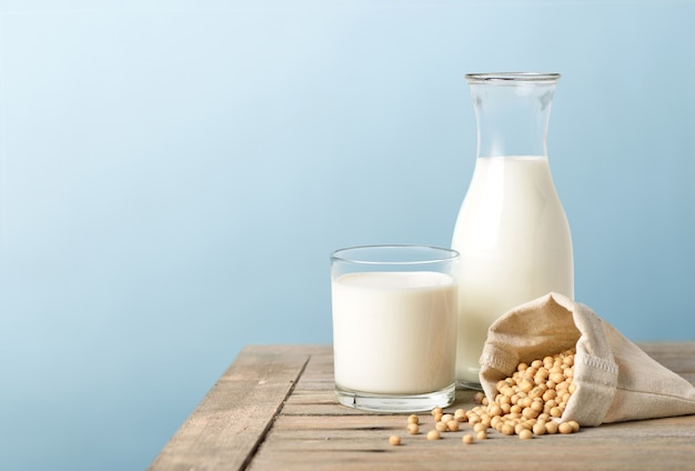 Glass of soy milk with bottle and soybeans Premium Photo