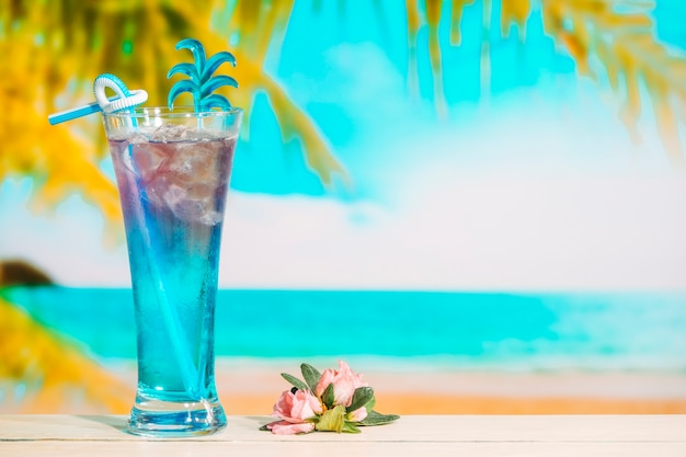Glass of tasty blue drink and pink flower Free Photo