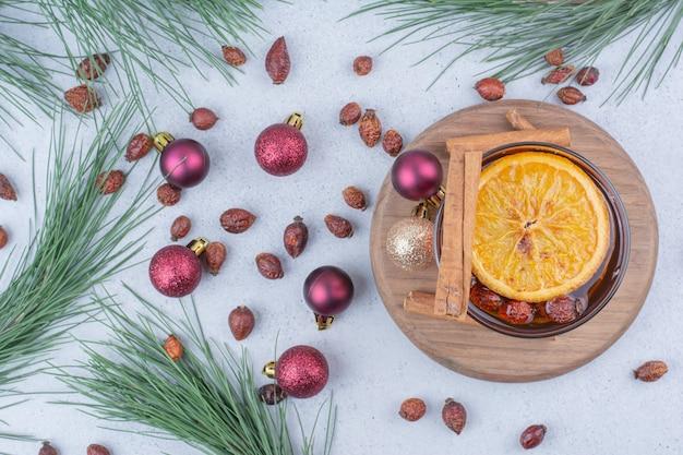 Bicchiere di tè con cinorrodi e palle di natale sulla superficie. Foto Gratuite