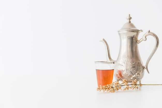 Glass of tea with teapot and branch Free Photo