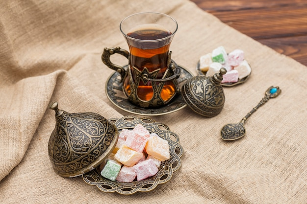 Free Photo | Glass of tea with turkish delight on canvas