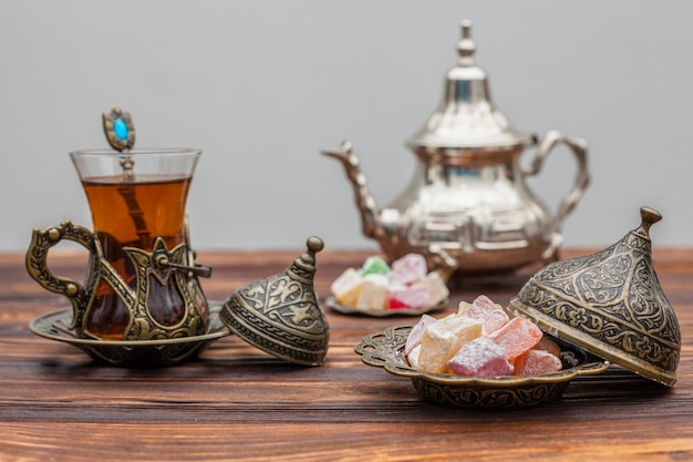 Glass of tea with turkish delight and teapot Free Photo