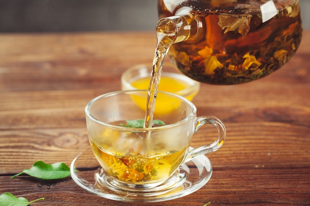 Glass teapot with cup of black tea on wooden table Premium Photo