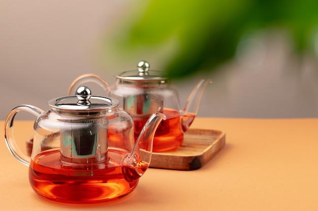 ぼやけた葉の背景に新鮮な紅茶とガラスのティーポット Premium写真