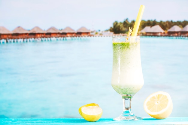 Glass of tropical green smoothie and sliced citrus Free Photo