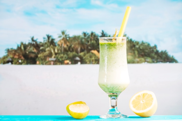 Glass of tropical sour smoothie and sliced citrus Free Photo