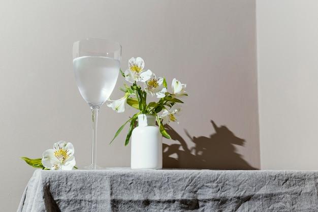 Bicchiere d'acqua e fiori sul tavolo Foto Gratuite
