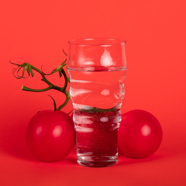 Glass of water surrounded by tomatoes Free Photo
