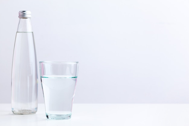Glass of water with a bottle on table Premium Photo