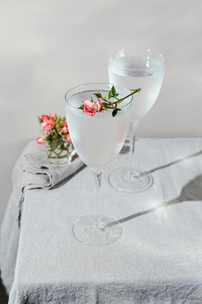 Bicchiere d'acqua con petali di fiori Foto Gratuite