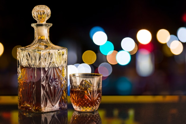 Glass of whiskey and bottle with bokeh effect Free Photo