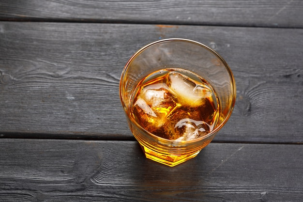 Glass of whiskey on ice with bottle on wood bar Premium Photo