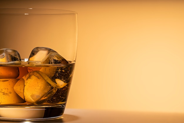 Glass of whiskey on the rocks ice close-up. or other alcohol: bourbon, cognac, or liqueur. orange background Premium Photo