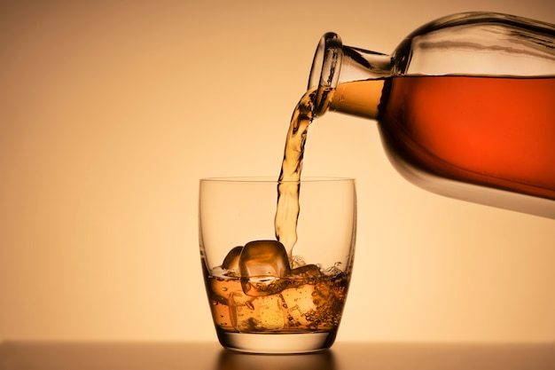 A glass of whiskey on the rocks. pouring bourbon or cognac from a liquor bottle. Premium Photo