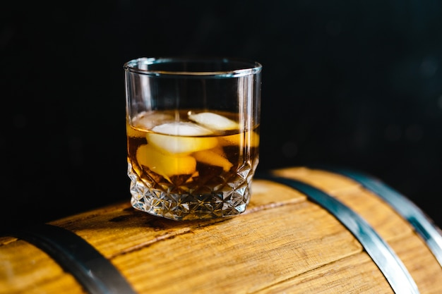 A glass of whiskey sitting on a wooden barrel Premium Photo